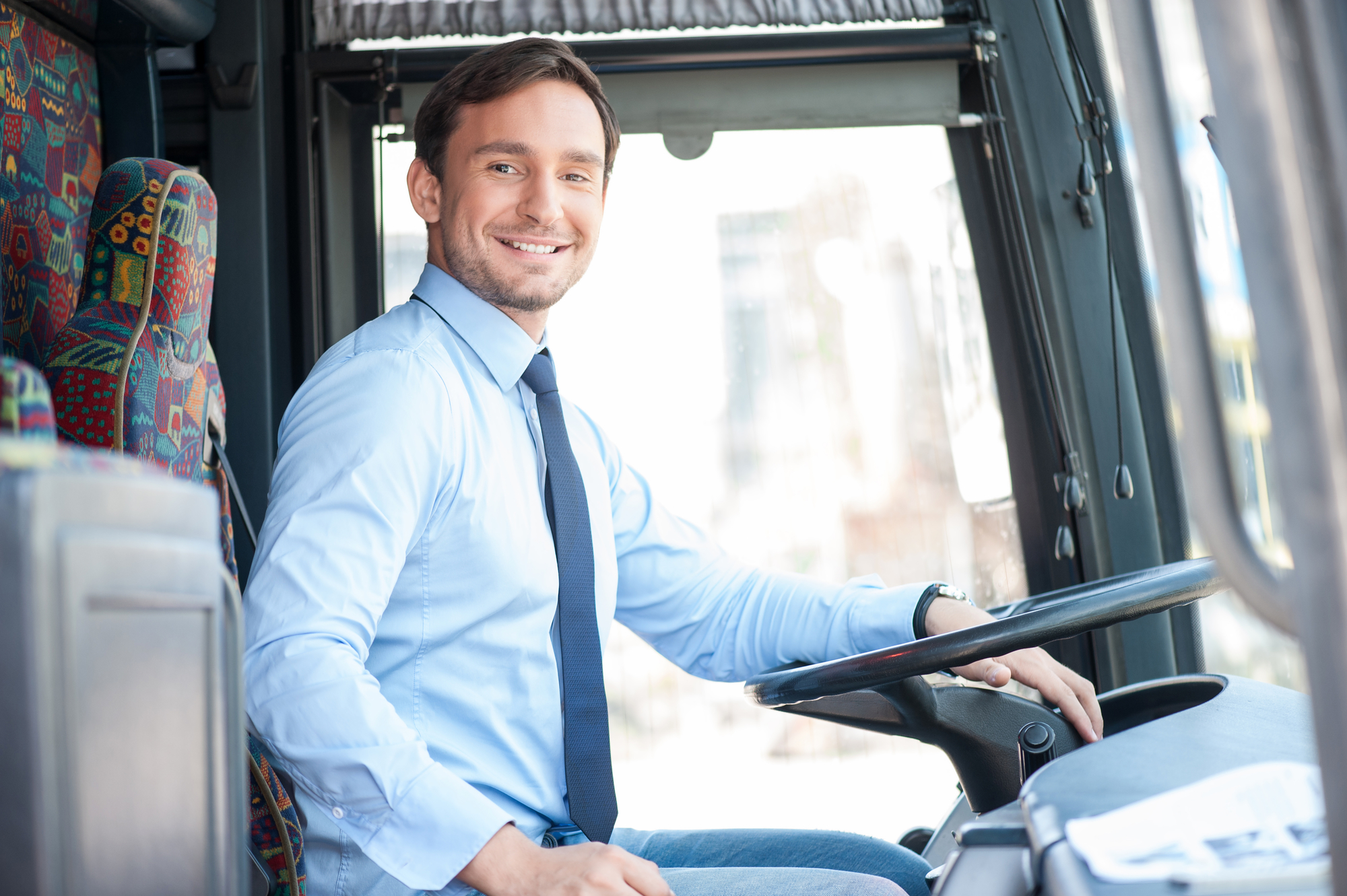 Handsome bus driver is sitting at steering wheel. He is looking at the camera and smiling